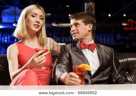 Young handsome man accompanied by elegant lady