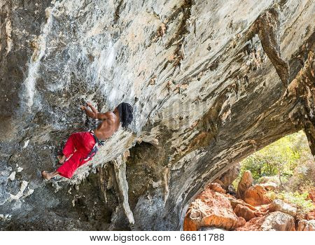 KRABI, THAILAND - MARCH 14, 2014: Rock climbers climbing on Railay beach in Krabi, Thailand. Railay beach is one of the most popular rock climbing locations in Asia.