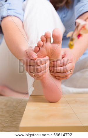 Hands doing feet reflexology or zone therapy at home
