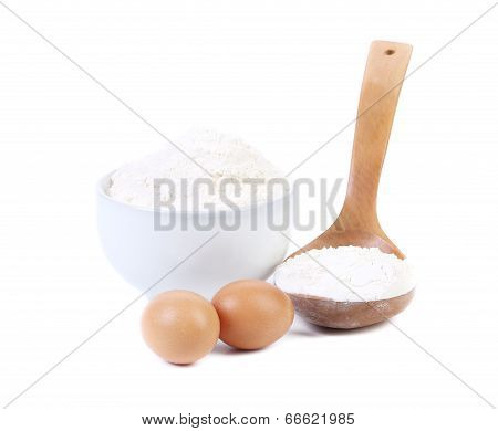 Spoon and bowl with flour two eggs.
