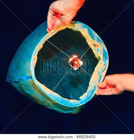 Man holds a chinese lantern as it begins to float