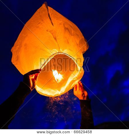 Man holds a chinese lantern as it begins to float and smokes comes off