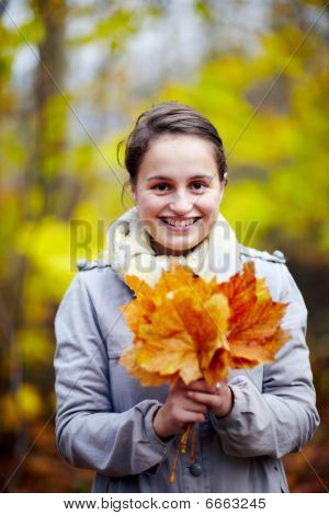 Cute Young Woman Holding Leaves In Forest