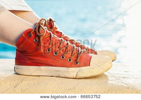 Red Sneakers On Girl And Seascape As Background