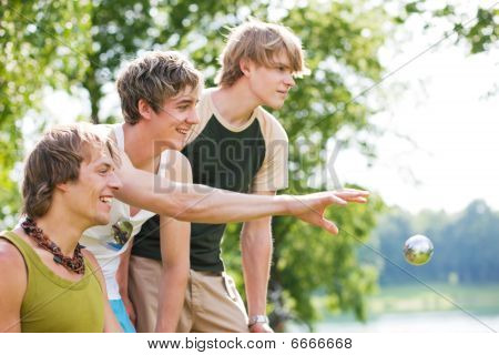 Group of young men playing boule at a lake