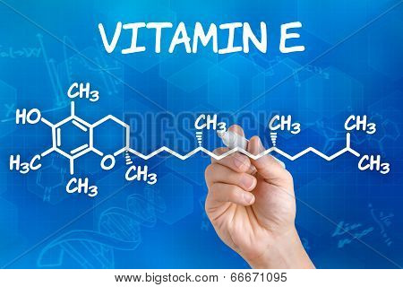 Hand with pen drawing the chemical formula of Vitamin E