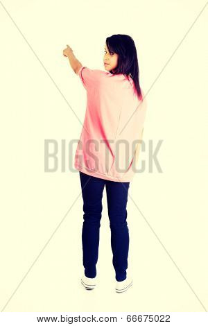 Happy , excited young woman pointing on copy space.
