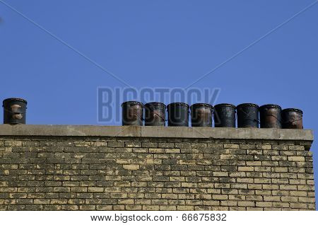 Old tar barrels on roof ledge