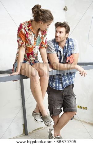 Young couple renewing home, talking in construction site, sitting on bar iron.