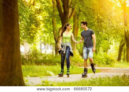 young couple in park ride rollerblades