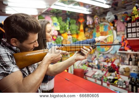 couple at amusement park playing shooting game