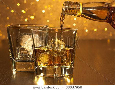 Barman Pouring Whiskey In Front Of Empty Whiskey Glass