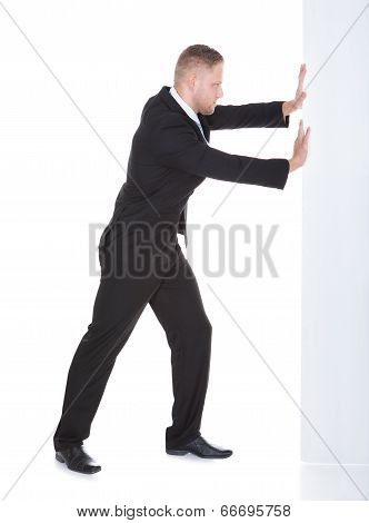 Businessman Pushing The Edge Of A Blank White Sign