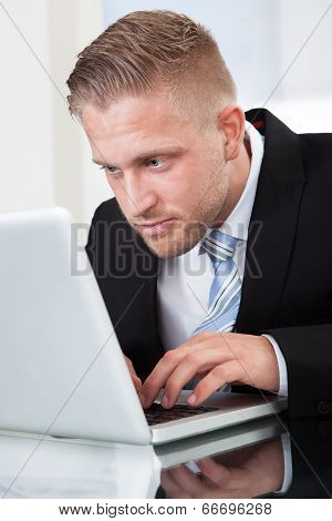 Businessman Leaning Forward At His Laptop Screen