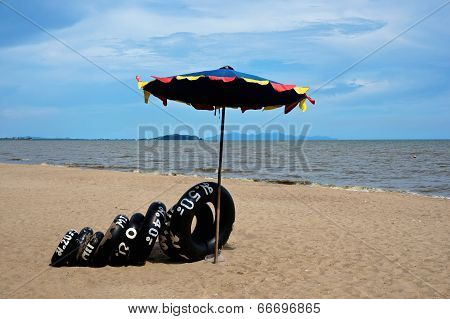 Black Inner Tube Under Umbrella At Sea