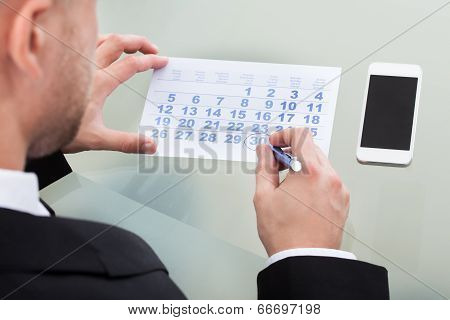 Businessman Marking His Dairy Schedule Checking For Appointments