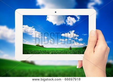 tablet computer in hand on the field backgrounds