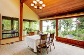 stock photo of log cabin  - Spacious dining area in log cabin house with high vaulted ceiling and wide window - JPG