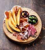picture of antipasto  - Antipasto snack ham melon and olives on wooden background - JPG