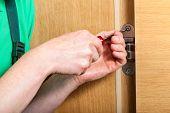 stock photo of hand drill  - Hands repairing a broken hinges in door - JPG