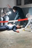 picture of crime scene  - Murder scene with two forensic analysts and a police lieutenant investigating a crime on a businessman in a basement - JPG