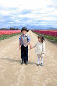stock photo of mary jane  - An adorable boy and girl holding hands on a dirt road in between tulip fields - JPG