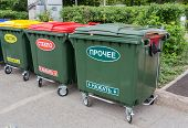 stock photo of dumpster  - Green dumpsters on a city street with inscription on russian - JPG