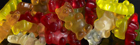 foto of gummy bear  - colorful pile of gummy bears in black back - JPG
