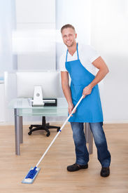 image of disinfection  - Handsome male janitor or cleaner cleaning the floor in an office building using a mop to wash the and disinfect the surface - JPG
