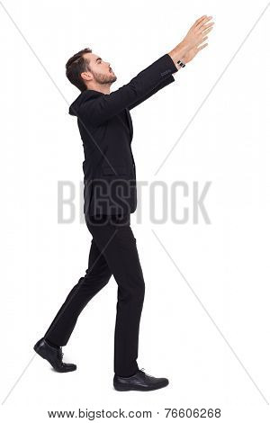 Businessman with arms raised catching something on white background