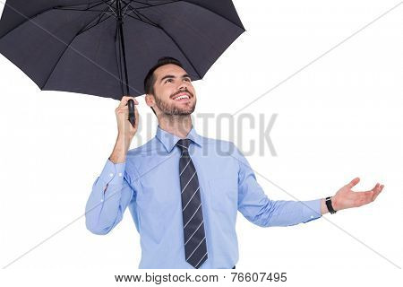 Happy businessman sheltering with a black umbrella on white background