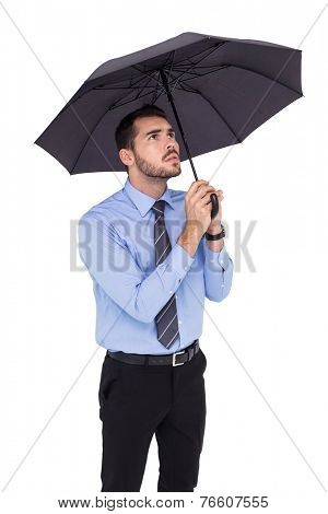 Anxious businessman sheltering with umbrella on white background