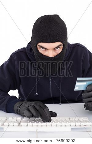 Concentrated burglar in balaclava shopping online on white background