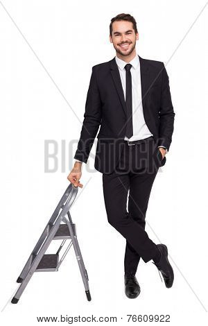 Smiling businessman leaning on stepladder on white background