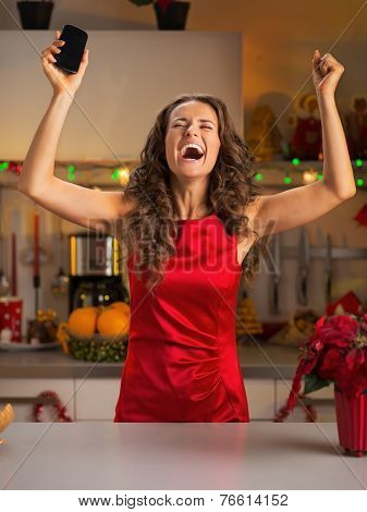 Happy Young Housewife With Cell Phone Rejoicing In Christmas Dec