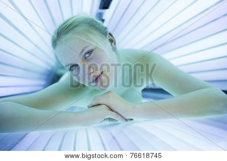Pretty, young woman tanning her skin in a modern solarium/sunbed. Getting an energy boost during dark winter days.
