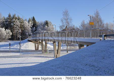 Concrete bridge crosses a road.