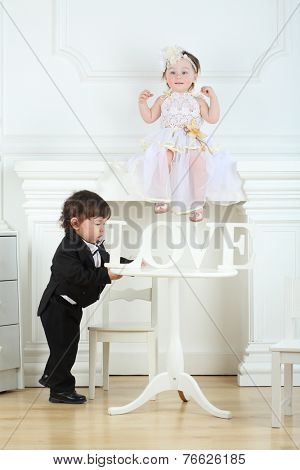 Little boy in black suit moving round table with wooden word love and girl in white dress sitting on ledge