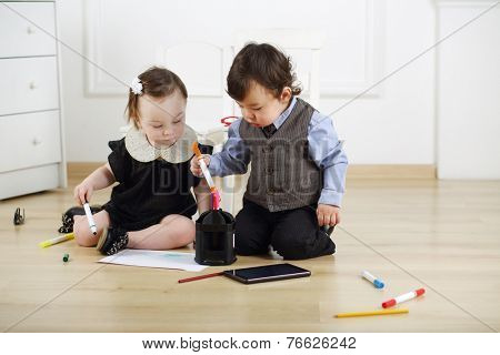 Two young children sitting on floor and draw colored markers