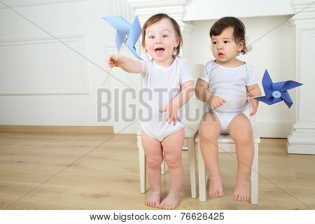 Two little kids sitting on white chairs with blue paper whirligigs