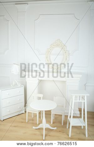 Interior white room with columns in ancient style, a fireplace and openwork frame, round table and chairs, commode and lamp