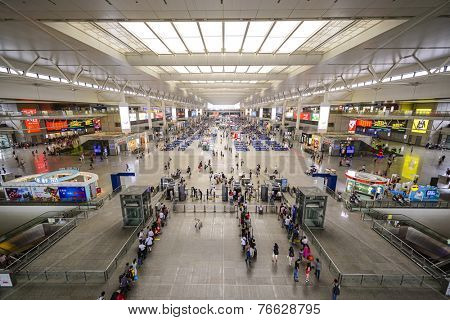 SHANGHAI, CHINA - JUNE 23, 2014: Passengers wait for trains in Shanghai Hongqiao Railway Station. It is the largest railway station in Asia with an area of 1.3 million square meters.