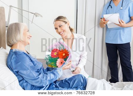 Happy daughter giving flower bouquet to sick mother at nursing home with caretaker in background