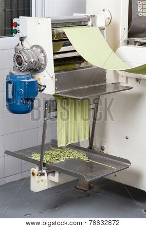 Green spaghetti pasta sheet being processed in automated machine at commercial kitchen