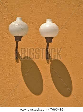 Two lamps with shadows on an orange wall