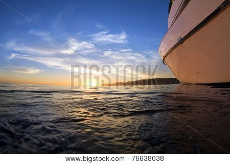 View of a sunset from the surface of the ocean shows a boat facing the beautiful horizon while nighttime ensures.