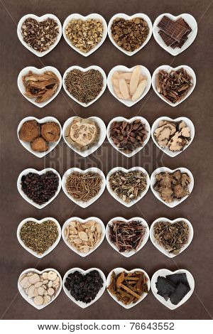 Large chinese herbal medicine selection in heart shaped porcelain bowls over lokta paper background.
