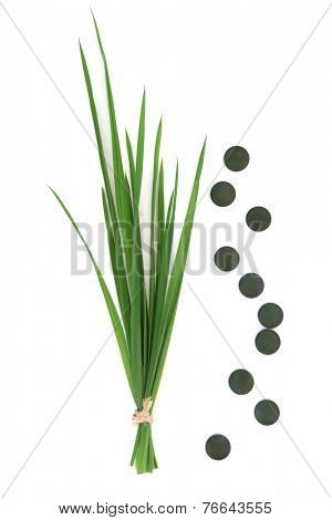 Chlorella tablets and wheat grass over white background.