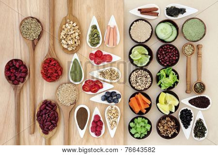 Large weight loss and diet super food selection in porcelain bowls and wooden spoons over beech wood board and mottled cream background.