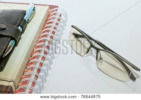 Note Book Pen And Glasses